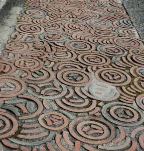 Wtopione w betonowy chodnik ceramiczne elementy